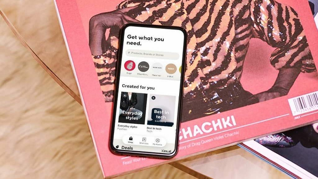 Phone showing Klarna app on coffee table