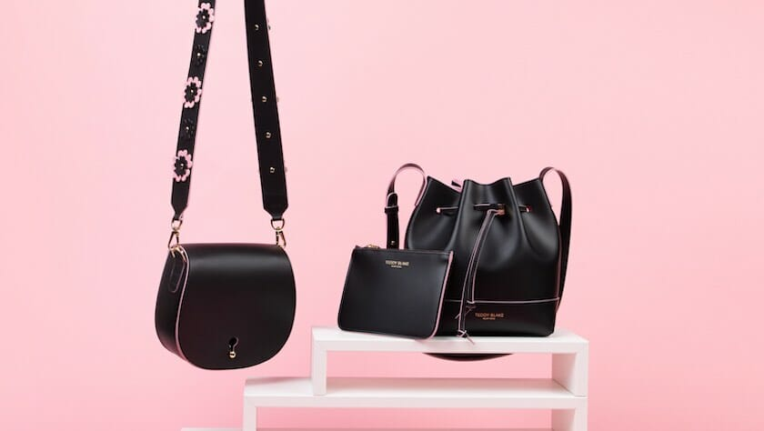 Two black leather handbags displayed on a pink background