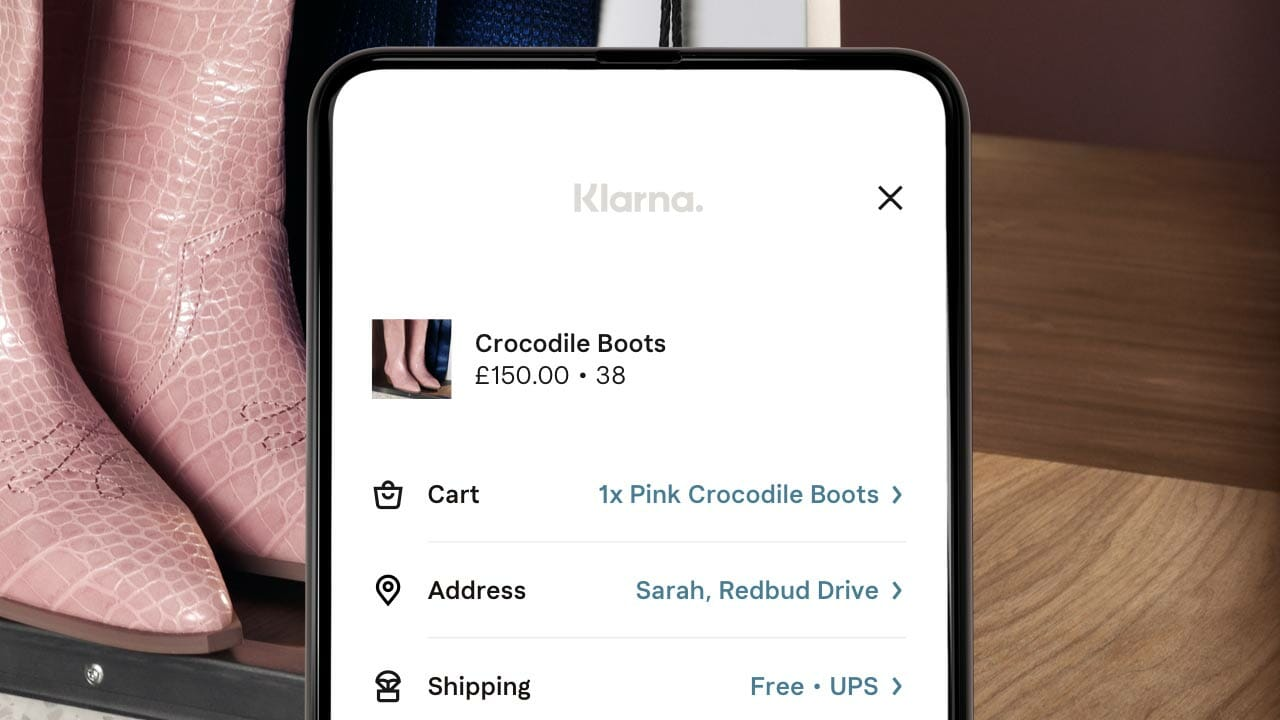 Pink cowboy boots being purchased with Klarna on a mobile