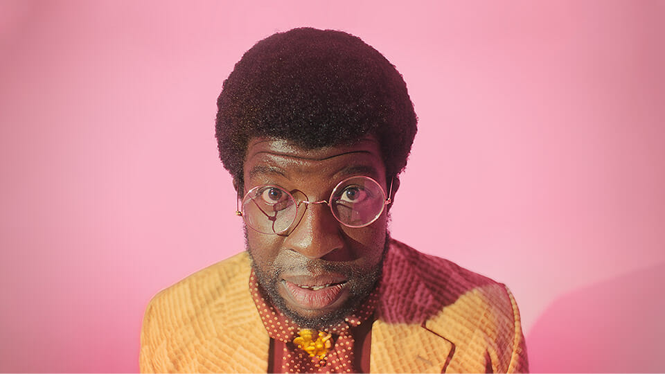 man with glasses on a pink background