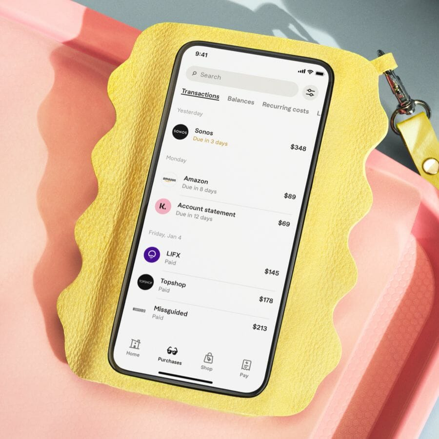 Mobile phone in a yellow case, on screen Klarna app transactions