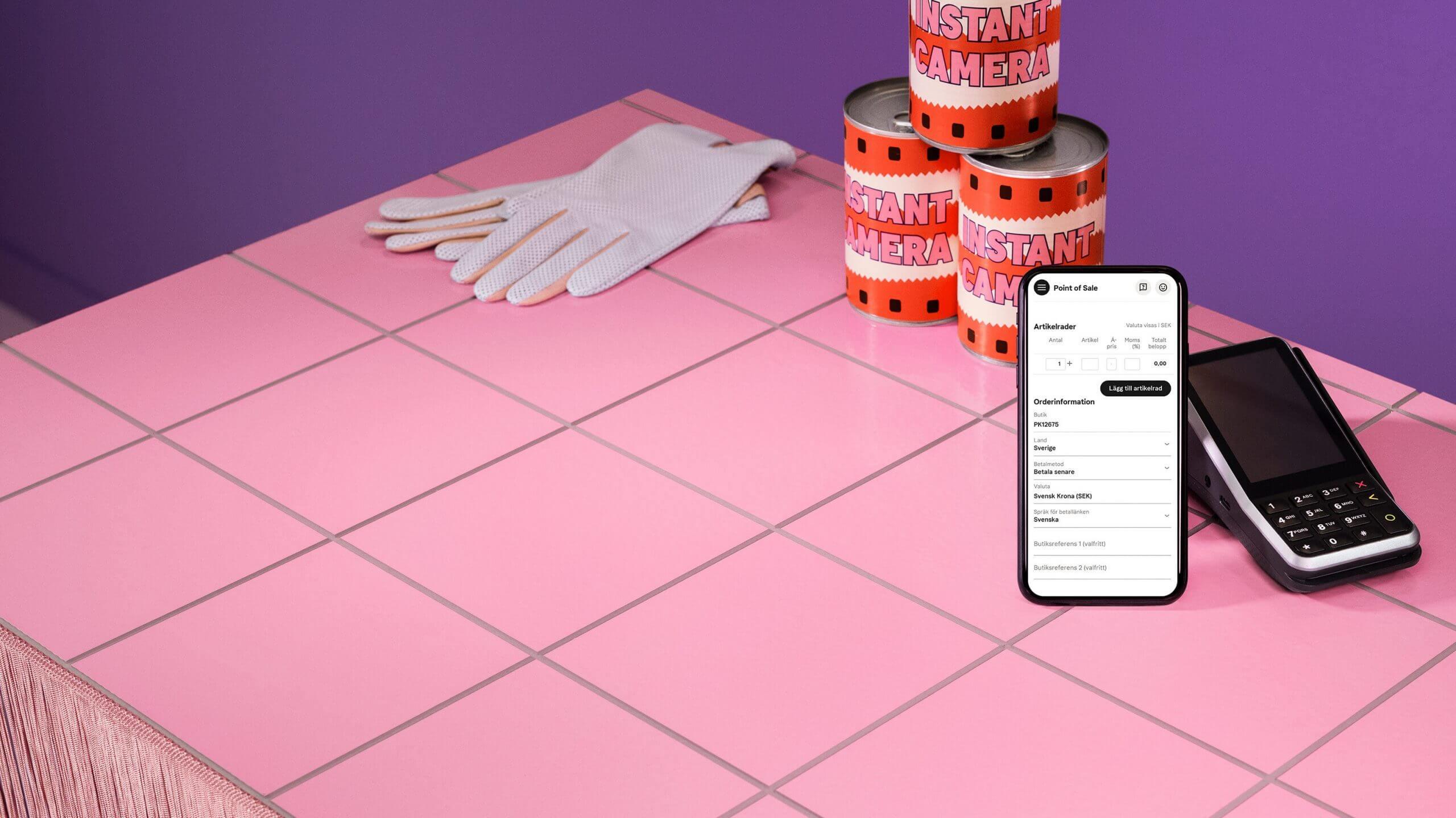 Point of sale appen i butiksportalen visas på telefonskärm, telefonen placerad rosa kakel
