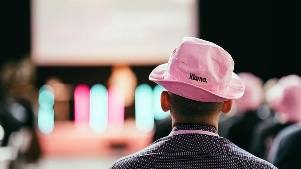 Ein Mann in einem rosa Klarna-Hut