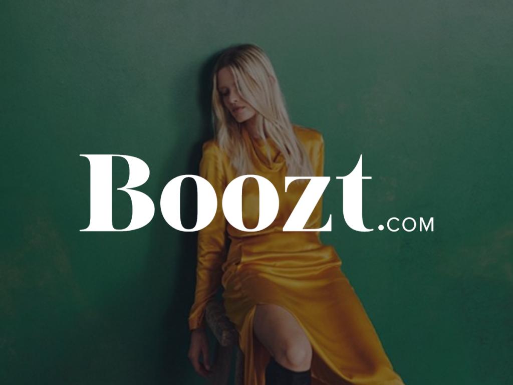 Nainen keltaisessa mekossa edessä valkoinen Boozt.com logo
