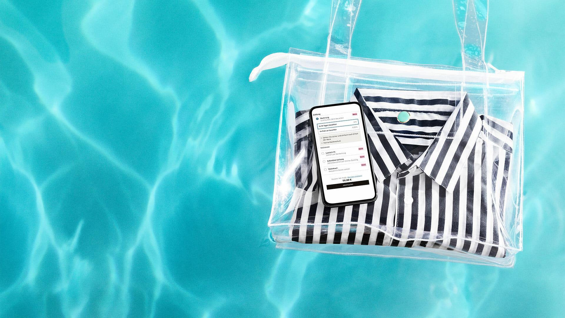 Kirkkaan sinistä vettä altaassa jossa kelluu läpinäkyvä laukku jossa raitapaita ja matkapuhelin