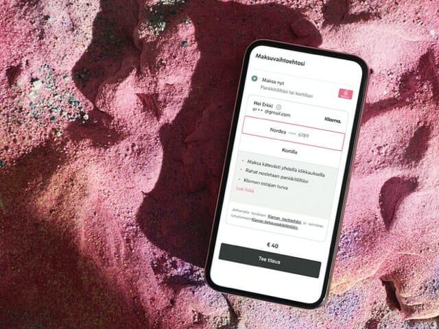 Pinkillä hiekalla matkapuhelin jonka näytöllä Klarna Chekout