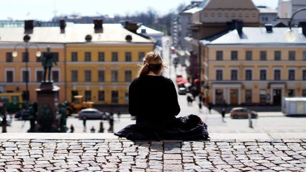 Tyttö istumassa ulkona portailla selin kuvaan