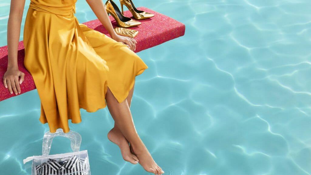 Nainen keltaisessa mekossa istuu ponnahduslaudalla altaalla