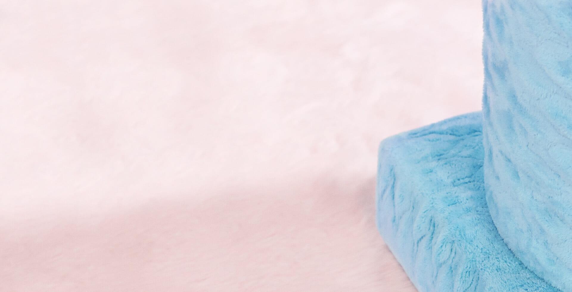 Vaaleanpunainen karvamatto ja vaalean sininen pehmeä pylväs