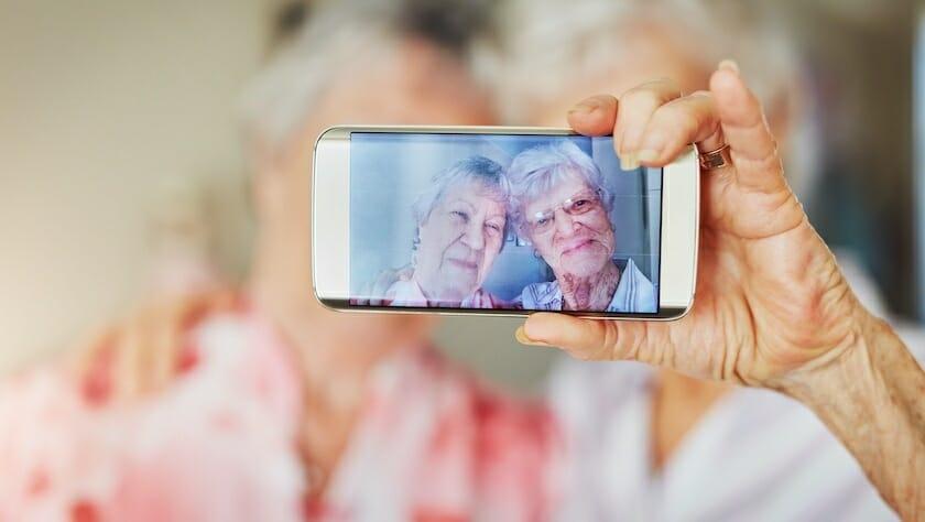 Kaksi seniori naista ottaa itsestään selfietä