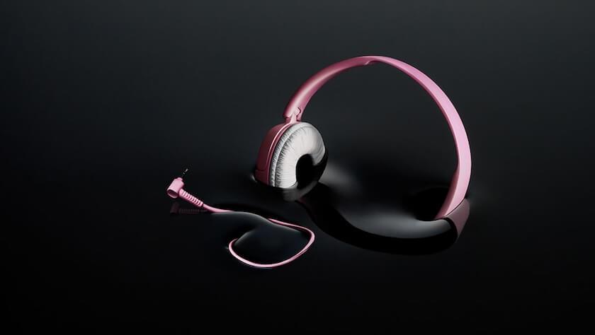 Black Friday - pinkit kuulokkeet uppoavat mustaan nesteeseen